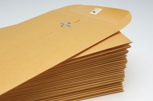 Stack of brown envelopes with clipping over white background