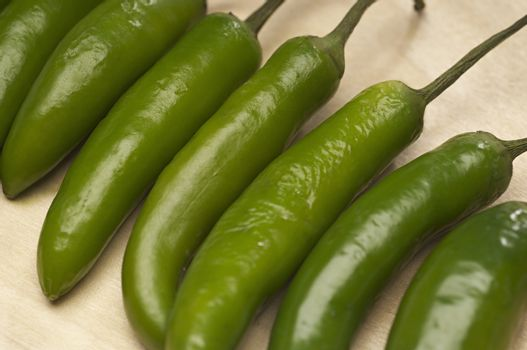Detail of green chili peppers in a row on chopping board