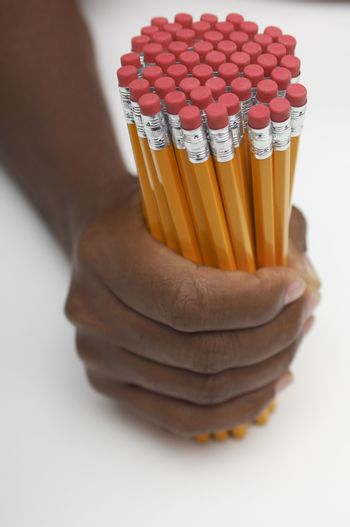 Closeup of man's hand holding group of pencils over white background