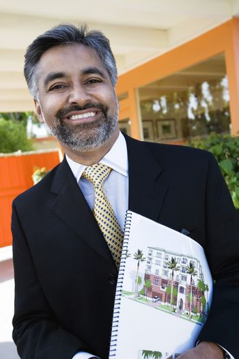 Portrait of a happy real estate agent with brochure