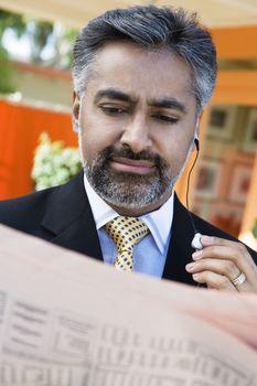 An Indian businessman reading newspaper