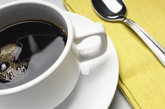 Closeup of refreshing coffee cup with napkin and spoon