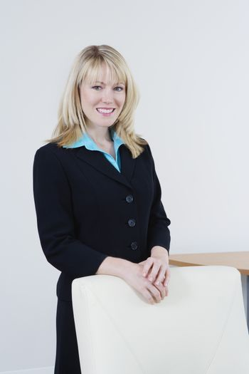 Portrait of a beautiful Caucasian business woman standing behind chair at office
