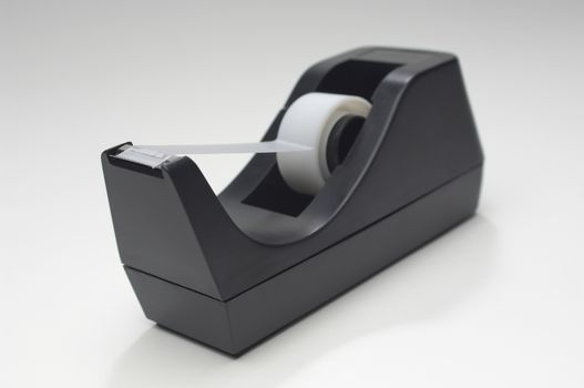 Closeup of a adhesive tape in holder over white background
