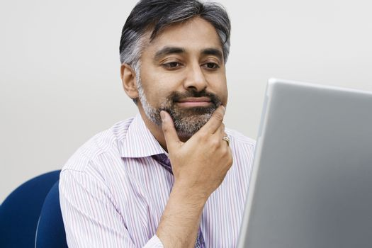 An Indian businessman using laptop in the office