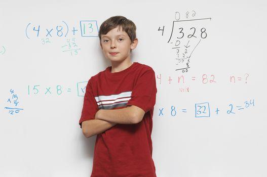 Schoolboy standing against whiteboard