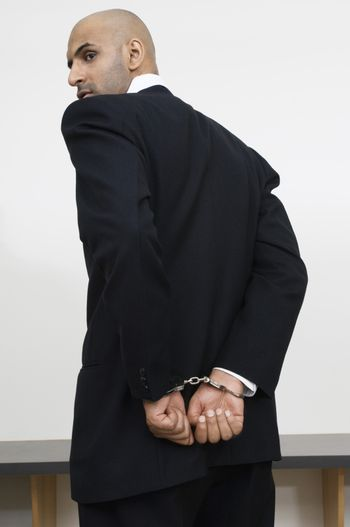 Businessman with handcuffs with bench in the background