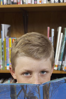 Boy peeking above book close-up view