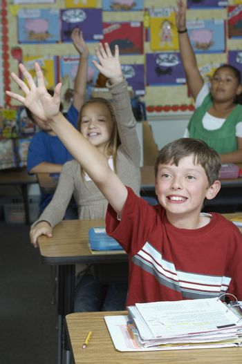 Four pupils with raised hands