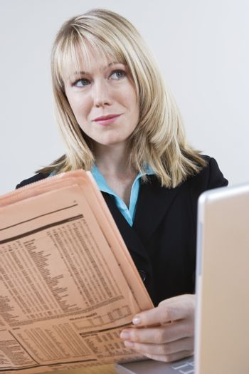 Caucasian businesswoman with newspaper and laptop looking away