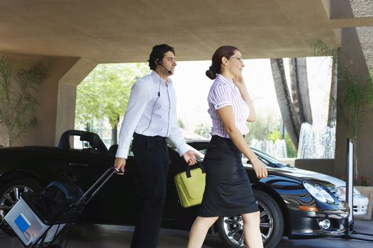 Business couple with luggage passing car