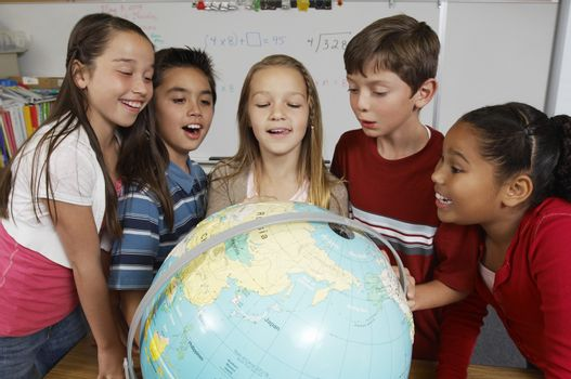 Group of pupils looking at globe