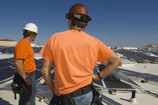 Electrical engineers among solar panels at solar power plant