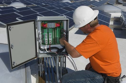 Electrical engineer repairing electricity box at solar power plant