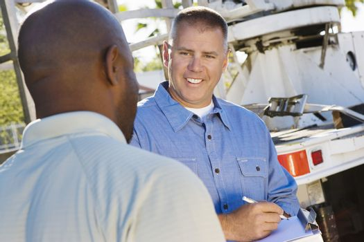 Mid-adult mechanic talking to co-worker