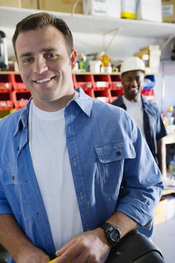 Portrait of an industrial worker with colleague at workplace