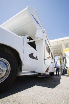 Man refueling recreational vehicle at petrol pump