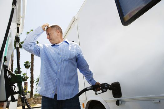 Male refueling recreational vehicle at gas station
