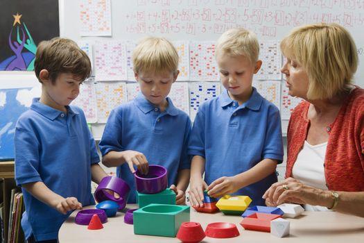 Teacher Helping Little Boys Assemble Educational Puzzle Toys