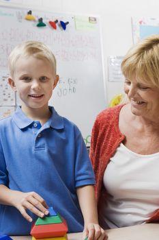 Teacher Watching Little Boy Assemble Educational Puzzle