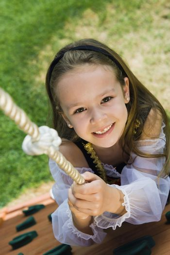 Dressed up Little Girl Climbing a Rope