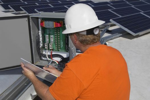 Electrical engineer writing notes while analyzing electricity box at solar power plant