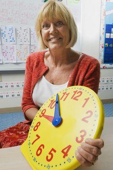 Teacher Holding a Time Teaching Clock