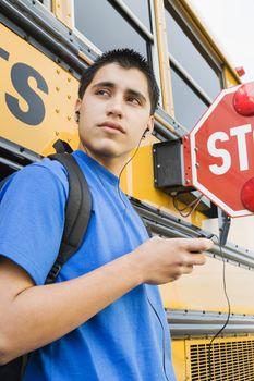 High School Boy With MP3 Player by School Bus