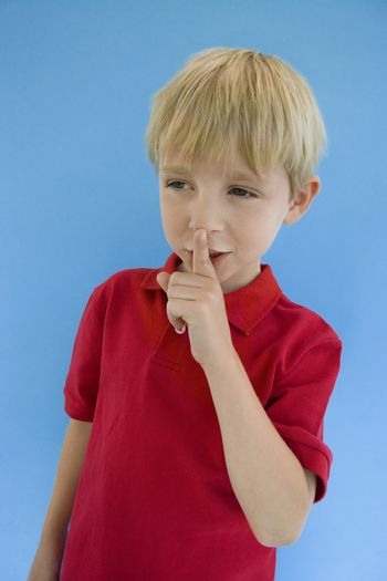 Cute little boy with finger on lips isolated over blue background