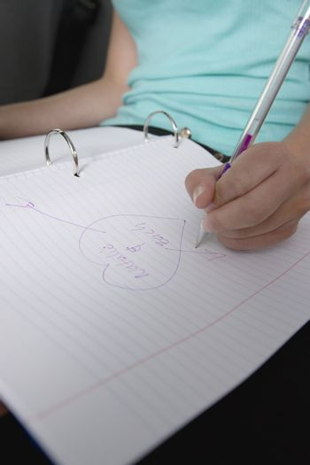 Teenage girl drawing a heart shape with crush's name in a notebook