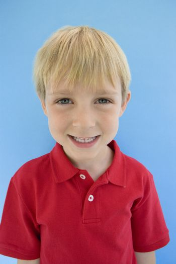 Portrait of a happy Caucasian boy isolated over blue background