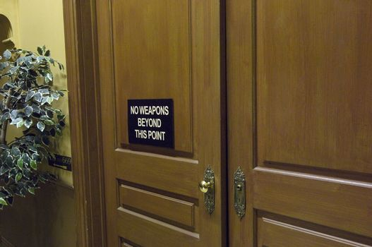 Closeup of a courtroom door with warning message on placard