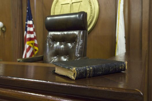 Holy Bible on table beside judge's chair in courtroom