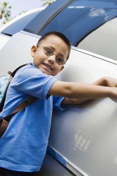 Boy Standing by Minivan
