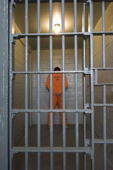 Prisoner standing in prison cell