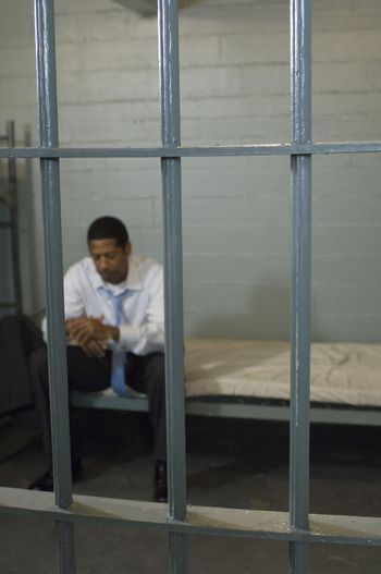 Man sitting in prison cell