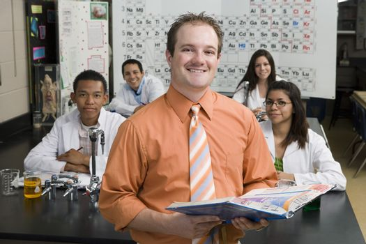 Portrait of a happy professor holding textbook with students in science class