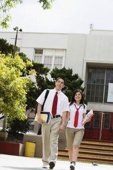 High School Couple Walking in Front of School