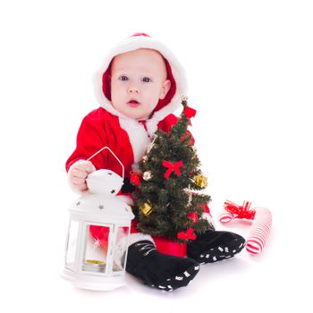 Little Santa boy with lantern and christmas tree isolated on white background