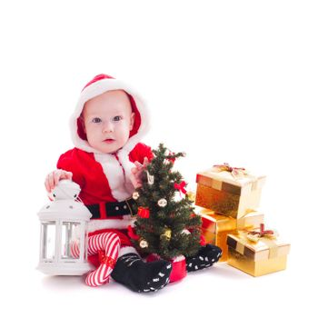 Little Santa boy with lantern, christmas tree and gift boxes isolated on white