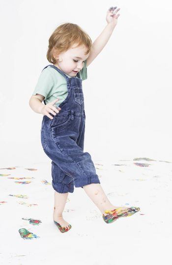 young child with paint on feet walking around
