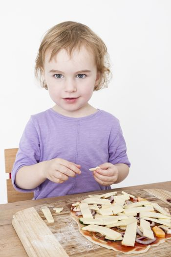 young child putting cheese on homemade pizza. studio shot with light grey background