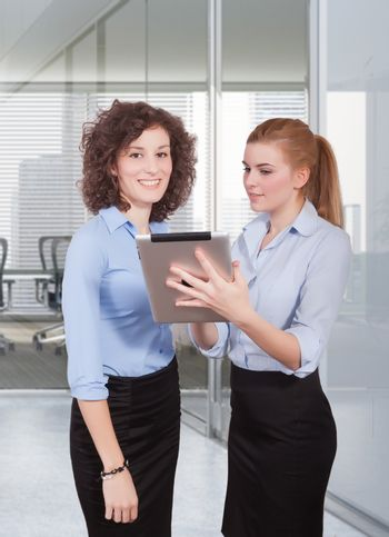 two woman using tablet in office