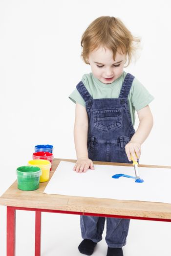 young girl working with paint on wooden desk. Studio shot in light grey background