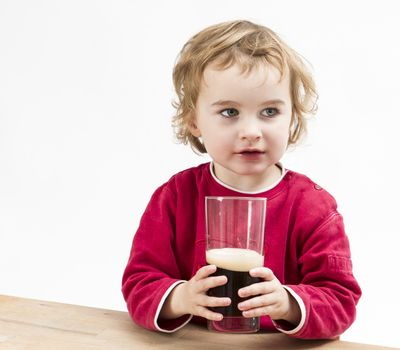young girl drinking beer in light background. studio shot