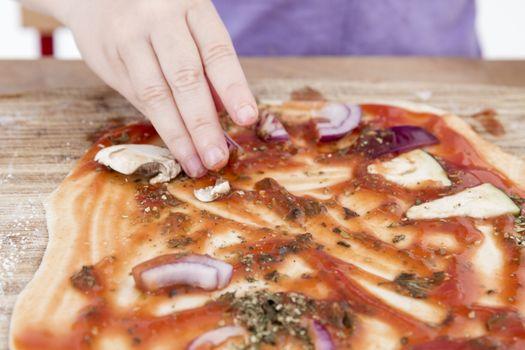 small hands preparing fresh pizza. studio shot.