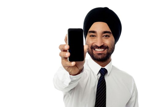 Salesman displaying newly launched mobile phone