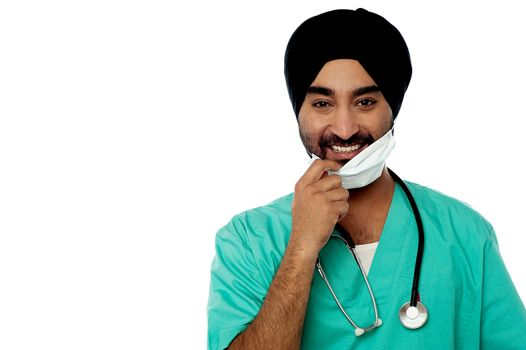 Smiling male doctor removing surgical mask