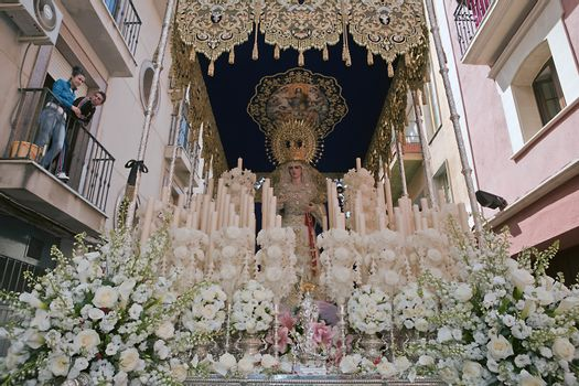 Front with candles, embroidered fabric and flowers of the throne of the Nuestra Señora del Amor Hermoso, Linares, Jaen province, Spain