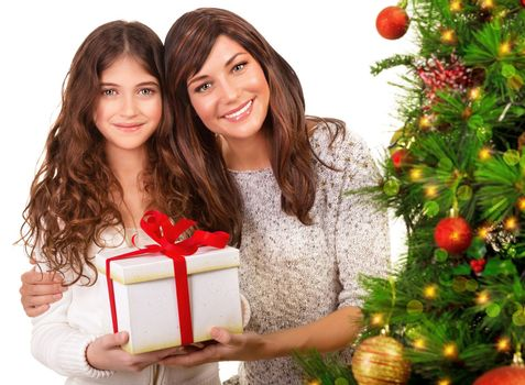 Closeup portrait of attractive mother with cute daughter holding in hands festive gift box, beautiful decorated Christmas tree, copy space